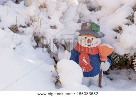 Snowman ceramic figure with hat and scarf in the snow