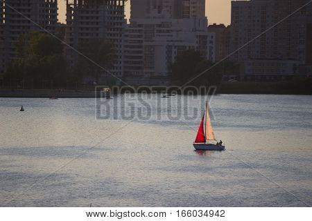 sailing boat with red sail in the city