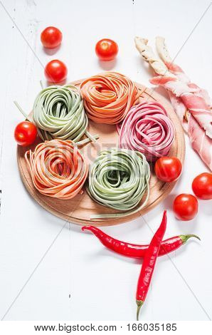 Colorful rolled pasta cherry tomatoes and bacon on the white wooden background