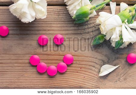 pink birth control tablet and flowers wooden table