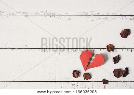 Red broken heart with dried rose petal on white wooden background