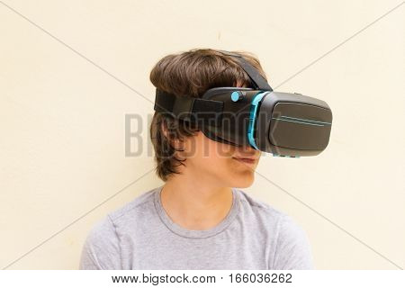 Teenager wearing VR virtual realty glasses close up