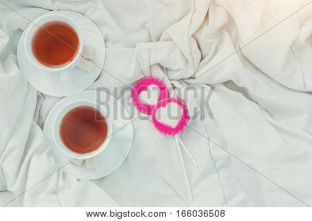 Breakfast in bed in Valentines day. Cup of tea and sweet candies. Love or holiday concept.