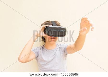 Teenager wearing and touching VR virtual realty glasses