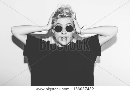 Stylish fashion sexy blonde bad girl surprised holding her head. Dressed in black t-shirt and rock sunglasses. Dangerous rocky emotional woman. Black and white toned. White background, not isolated
