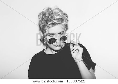 Stylish fashion sexy blonde bad girl in a black t-shirt and rock sunglasses smokes. Dangerous rocky emotional woman. Black and white toned. White background, not isolated