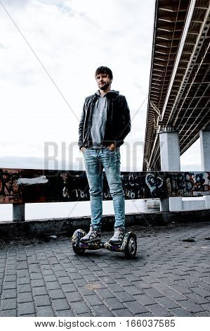 trendy guy standing on gyro scooter on a background of the bridge