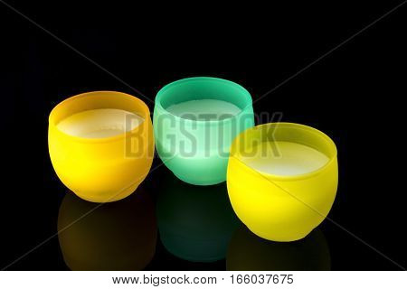 Three candles in yellow and turquoise on a black background