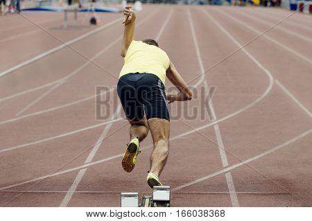 athlete runner explosive start to sprint from starting blocks