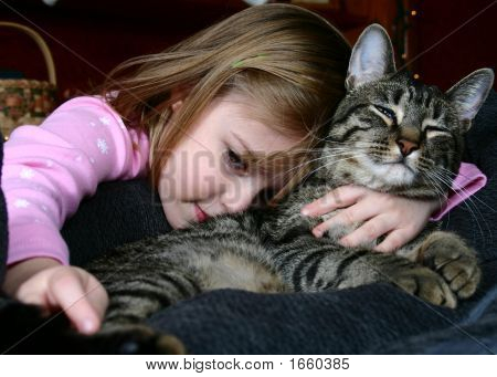 Adorable little girl snuggling with her pet cat. poster
