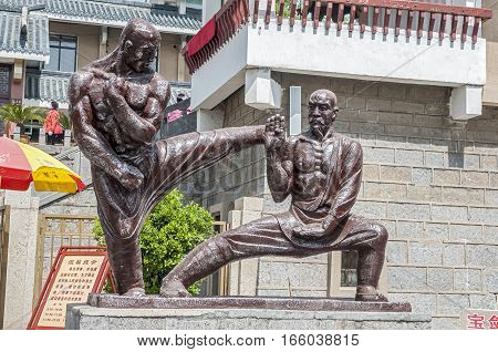 China the Shaolin Monastery. The sculptural group of two kung fu fighters in combat.