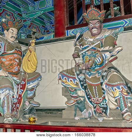 China the Shaolin Monastery.On the reverse side of the gate to the Hall of the Heavenly Ruler are 4 celestial ruler. Dhrtarashtra (with a lute) and Virudhaka (with a sword).