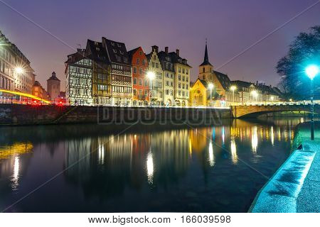 Picturesque quay and church of Saint Nicolas with mirror reflections in the river Ile during evening blue hour, Strasbourg, Alsace, France