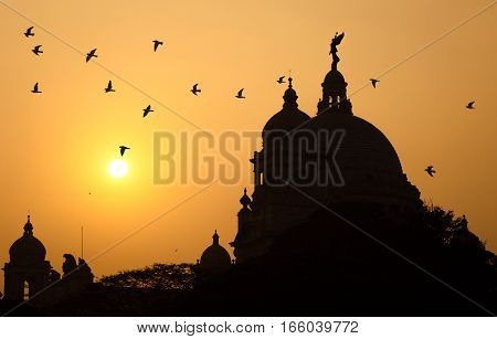 Silhouette Victoria Memorial dome with flying birds at sunrise - Good morning message content.