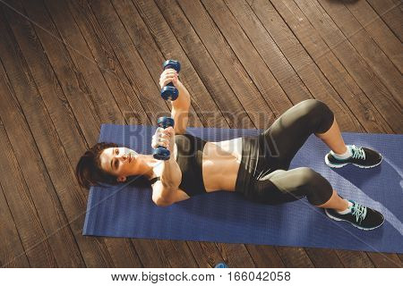 Young athletic woman training hard with dumbells at home, lying at mat. upper view