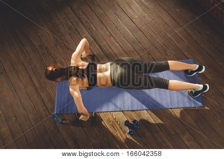 Young athletic woman training hard with gym exercise at home, lying at mat. top view