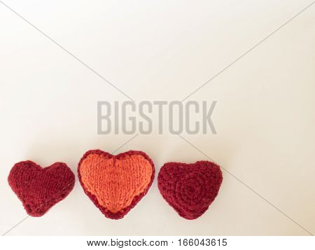 Red and orange knit wool hearts on a white background