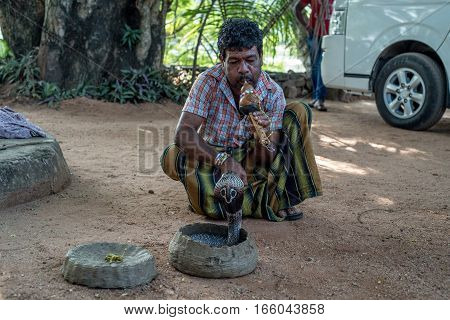 POLONNARUWA, SRI LANKA - CIRCA DECEMBER 2016: Snake enchanter or fakir plays pipe to enchant cobra. Polonnaruwa is an ancient capital of Sinhalese kingdom, UNESCO World Heritage Site.