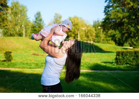 Happy Mother throws baby girl into the air in nature
