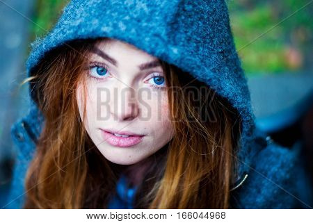 Calm beautiful blue-eyed girl in the hood. Portrait of a beautiful girl.