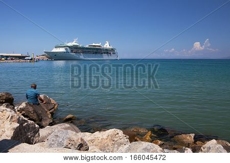 KUSADASI, GREECE - MAY 17, 2016: A fisherman tries his luck in sight of a docked cruise ship