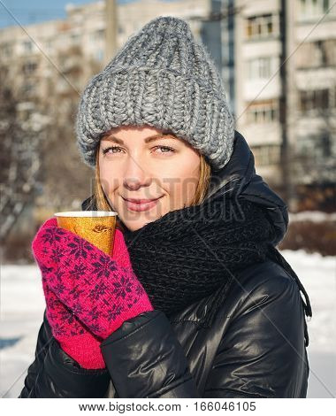 Girl drinks hot coffee outdoors in winter time