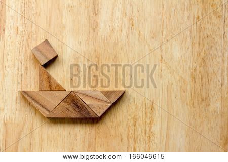 Tangram puzzle in human on boat shape on wooden background