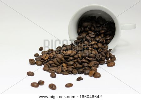 white porcelain cup with coffee beans spilled isolated on white background