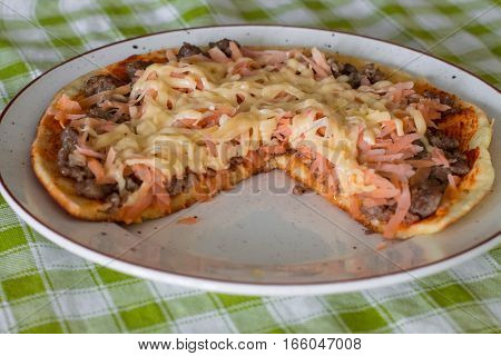 Cutting frittata with tomato sauce, carrot, fried minced beef and cheese on white plate on green checkered napkin.