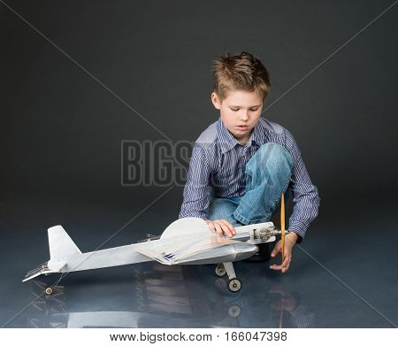Kid playing with handmade plane glider. Pre-teen boy holding a wooden plane model.