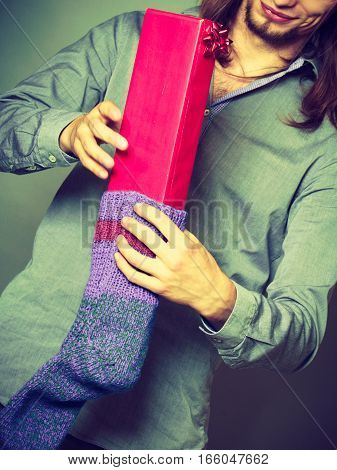 Holiday xmas winter time season. Stylish guy putting wrapped gift in knitted christmas sock