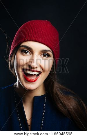Portrait of pretty girl in red hat. She smiles and feels happy. Optimism. Studio shot of a magnificent young woman in a fitting dress and elegant classic hat. Beauty fashion concept.