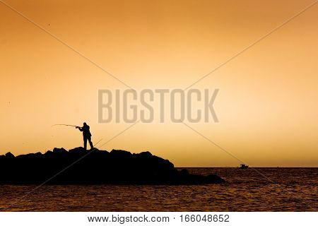a fisherman is standing by the sea at sunrise. backlit, toned orange.
