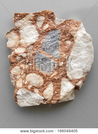 Piece of breccia rock isolated over grey background. Sedimentary rock coming from Malaga mountains Spain