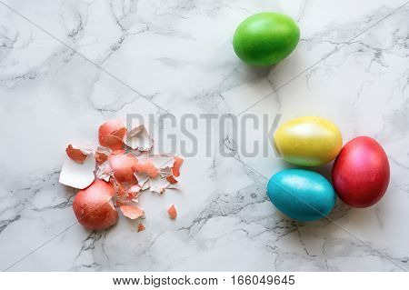 Colorful easter eggs on marble table. Broken red egg shell.