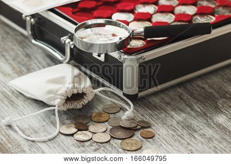 Different collector's coins with a magnifying glass and money bag soft focus background