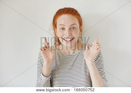 Headshot Of Superstitious Redhead Girl Keeping Her Fingers Crossed, Making Wish, Sincerely Believing
