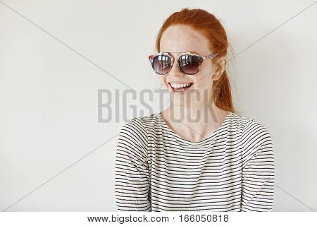 Cheerful Hipster Girl With Freckles And Ginger Hair Wearing Stylish Shades And Sailor Shirt Smiling