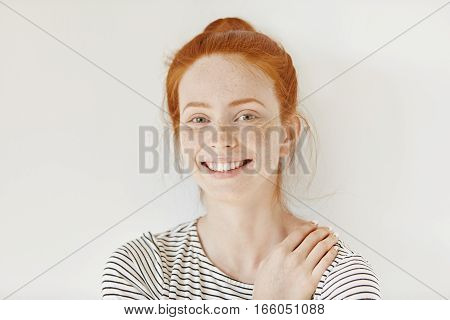 Stylish Freckled Teenage Girl With Hair Knot Having Fun Indoors And Looking At Camera With Cheerful