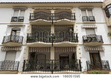 Ronda (Andalucia Spain): facade of old typical residential building with balconies verandas and potted plants and flowers