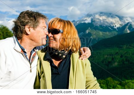 a senior couple is kissing in front of a nice view of the mountains in berchtesgaden bavaria, germany