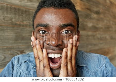 Omg! Portrait Of Astonished And Amazed Young African Man In Denim Shirt Holding Hands On His Cheek,