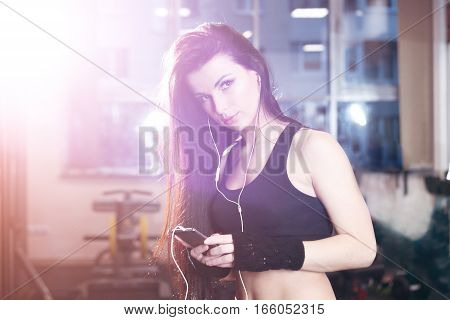 Sexy Fitness Woman In Sportswear Resting After Dumbbells Exercises In Gym. Beautiful Girl Chatting O