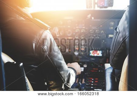 Two Unrecognizable Jet Airliner Pilots Wearing Leather Jackets Piloting Aircraft At Sunset, Sitting