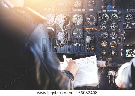 Airplane Crew Sitting In Cockpit With Papers, Filling In Documention Before Performing Flight. Rear