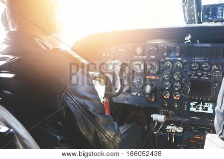 Piloting Aircraft. Back View Of Unrecognizable Commercial Pilot Wearing Leather Jacket And Headset S