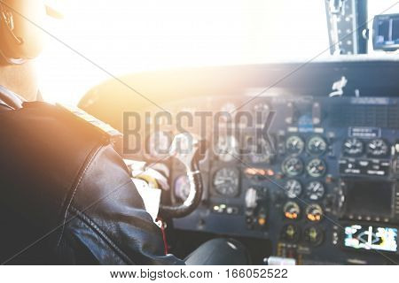 Caucasian Aviator Piloting Airplane. Rear View Of Commercial Pilot Wearing Headset And Leather Jacke