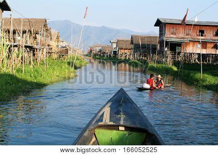 Maing Thauk (lake Inle) Myanmar - 15 January 2010: People on rowing a boat at the village of Maing Thauk on lake Inle Myanmar