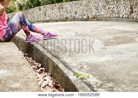Cropped Shot Of Fashionable Young Woman Runner Wearing Pink Top, Space Print Leggings And Purple Run