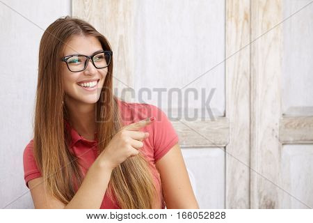 Indoor Shot Of Attractive Young Caucasian Woman Wearing Stylish Eyeglasses Smiling Happily, Having F